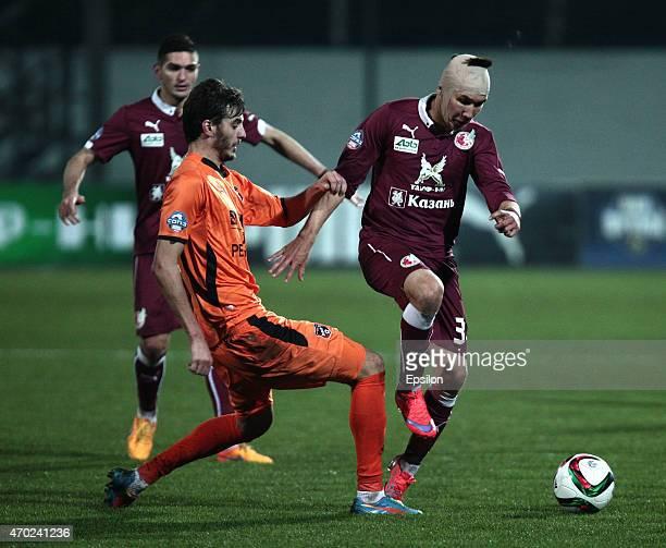 Elmir Nabiullin of FC Rubin Kazan is challenged by Aleksandr Yerokhin of FC Ural Sverdlovsk Oblast during the Russian Premier League match between FC...