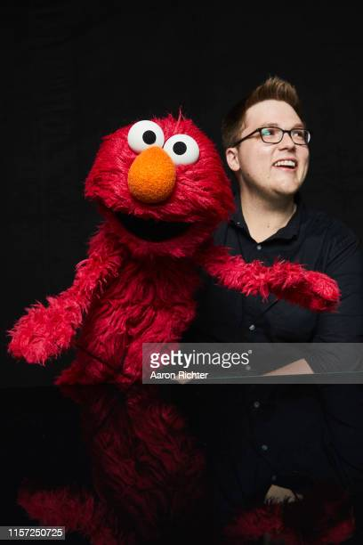 """July 19: Elmo and Ryan Dillon of """"Sesame Street"""" pose for a portrait in the Pizza Hut Lounge at 2019 Comic-Con International: San Diego on July 19,..."""