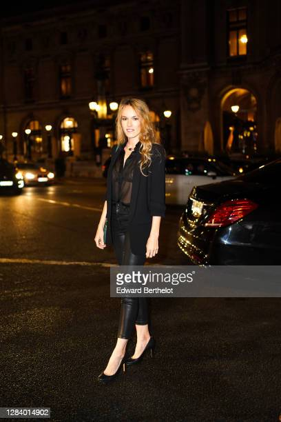 Elodie Fontan wears a black oversized blazer jacket, a mesh shirt, black shiny leather leggings, black high heeled pointy shoes, a necklace, outside...