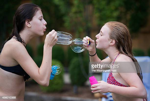 Eloise Lancsweert 15 and Evie Wolfe 13 blow bubbles during a barbecue at Greta De Keyser and Chef Bart Vandaele's home in Alexandria Virginia on...