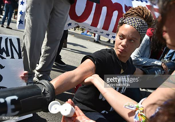 Elokin Cheung puts suntan lotion on Shayna Cureton while protesters block a street with interlocked hands outside the Hyatt Regency Hotel where US...