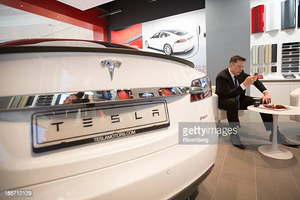 Elon Musk billionaire cofounder and chief executive officer of Tesla Motors Inc checks a mobile device as a Tesla Model S automobile sits on display...