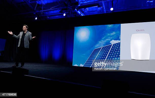 Elon Musk CEO of Tesla with a Powerwall system on display unveils suite of batteries for homes businesses and utilities at the Tesla Design Studio...