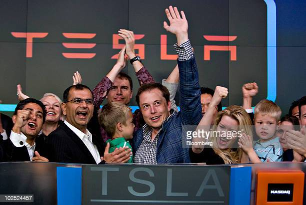 Elon Musk, chairman and chief executive officer of Tesla Motors, center, participates in the opening bell ceremony at the Nasdaq Marketsite with his...