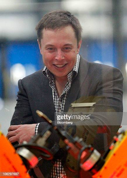 Elon Musk chairman and chief executive officer of Tesla Motors Inc looks at a robot arm display during a tour of the new Tesla Motors auto plant...