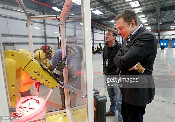 Elon Musk chairman and chief executive officer of Tesla Motors Inc looks at a robot display during a tour of the new Tesla Motors auto plant formerly...