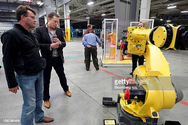 Elon Musk chairman and chief executive officer of Tesla Motors Inc center looks at a robot arm display during a tour of the new Tesla Motors auto...