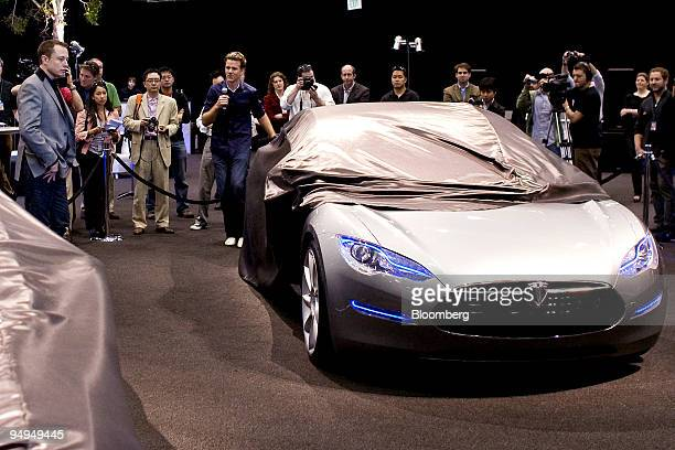Elon Musk chairman and chief executive officer of Tesla Motors Inc left looks on as the Tesla Model S electric car is unveiled at the Space...