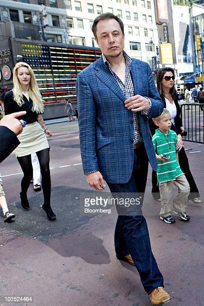 Elon Musk, chairman and chief executive officer of Tesla Motors, walks outside the Nasdaq Marketsite followed by fiancee Talulah Riley, left, in New...