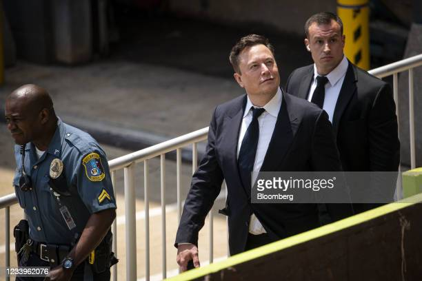 Elon Musk, chief executive officer of Tesla Inc., center, departs court during the SolarCity trial in Wilmington, Delaware, U.S., on Tuesday, July...