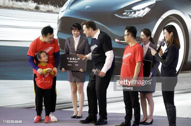 Elon Musk chief executive officer of Tesla Inc center greets a customer during the Tesla ChinaMade Model 3 Delivery Ceremony at the company's...