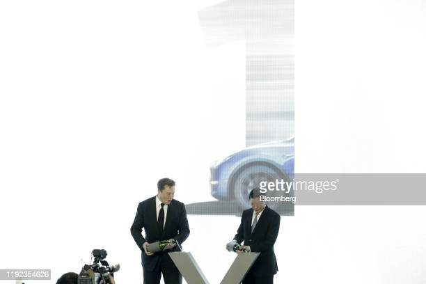 Elon Musk chief executive officer of Tesla Inc left and Ying Yong mayor of Shanghai pour champagne during the Tesla ChinaMade Model 3 Delivery...