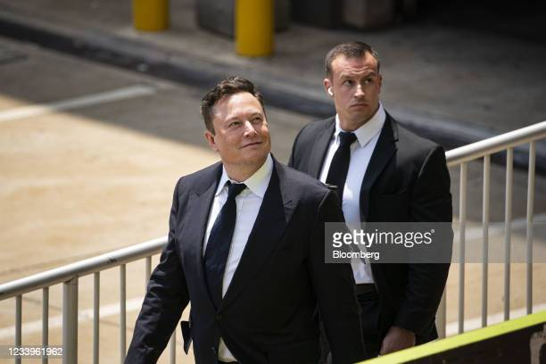 Elon Musk, chief executive officer of Tesla Inc., left, departs court during the SolarCity trial in Wilmington, Delaware, U.S., on Tuesday, July 13,...