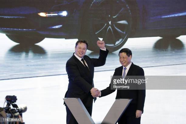 Elon Musk chief executive officer of Tesla Inc left gestures while shaking hands with Ying Yong mayor of Shanghai during the Tesla ChinaMade Model 3...