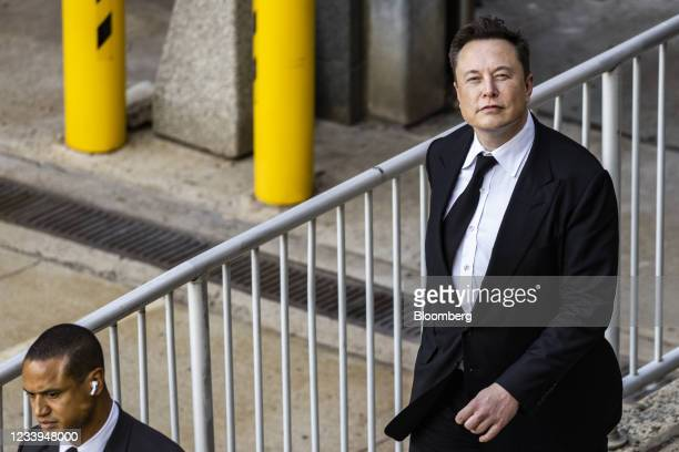 Elon Musk, chief executive officer of Tesla Inc., right, departs from court for the SolarCity trial in Wilmington, Delaware, U.S., on Monday, July...