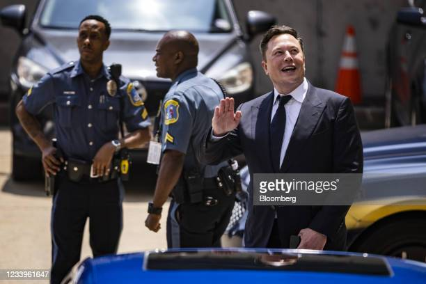 Elon Musk, chief executive officer of Tesla Inc., right, waves while departing court during the SolarCity trial in Wilmington, Delaware, U.S., on...