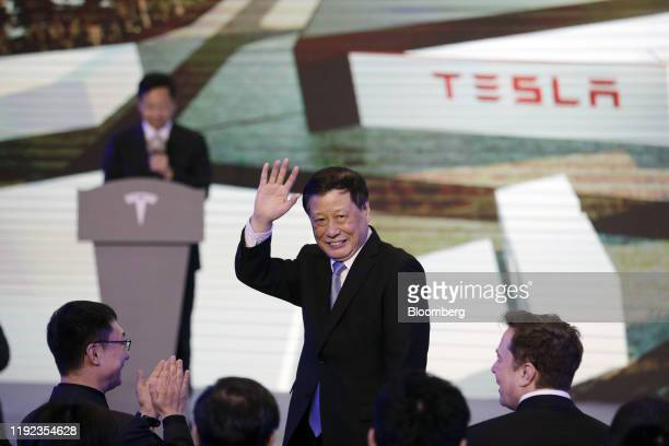 Elon Musk chief executive officer of Tesla Inc seated right watches Ying Yong mayor of Shanghai wave to attendees during the Tesla ChinaMade Model 3...