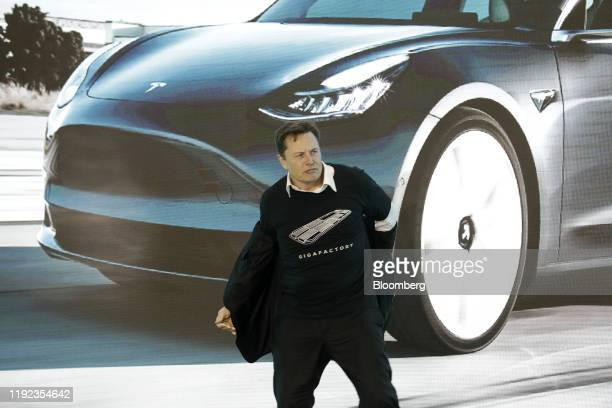 Elon Musk chief executive officer of Tesla Inc takes off his jacket during the Tesla ChinaMade Model 3 Delivery Ceremony at the company's Gigafactory...