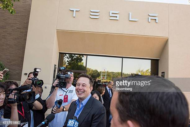 Elon Musk cofounder and chief executive officer of Tesla Motors Inc center laughs as he talks with members of the media after meeting Shinzo Abe...