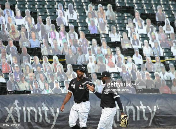 Eloy Jimenez and Luis Robert of the Chicago White Sox celebrate an inningending catch in front of cutout fans during an exhibition game against the...