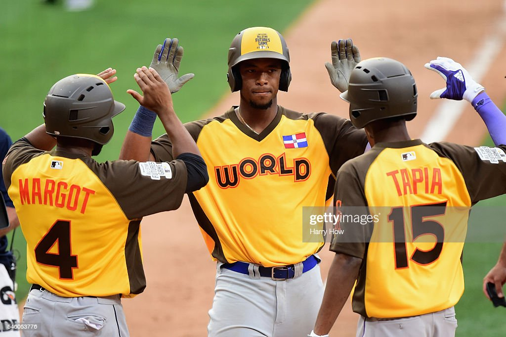 Eloy Jimenez #27 of the Chicago Cubs and the World Team is congratulated after scoring during the SiriusXM All-Star Futures Game at PETCO Park on July 10, 2016 in San Diego, California.