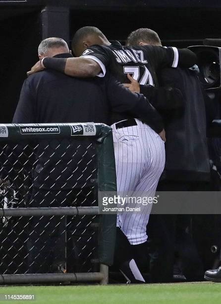 Eloy Jimenez of the Chicago White Sox is helped to the locker room after hitting the wall trying to catch a home run ball hit by Grayson Greiner of...