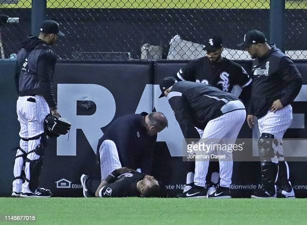 Eloy Jimenez of the Chicago White Sox is tended to after hitting the wall trying to catch a home run ball hit by Grayson Greiner of the Detroit...