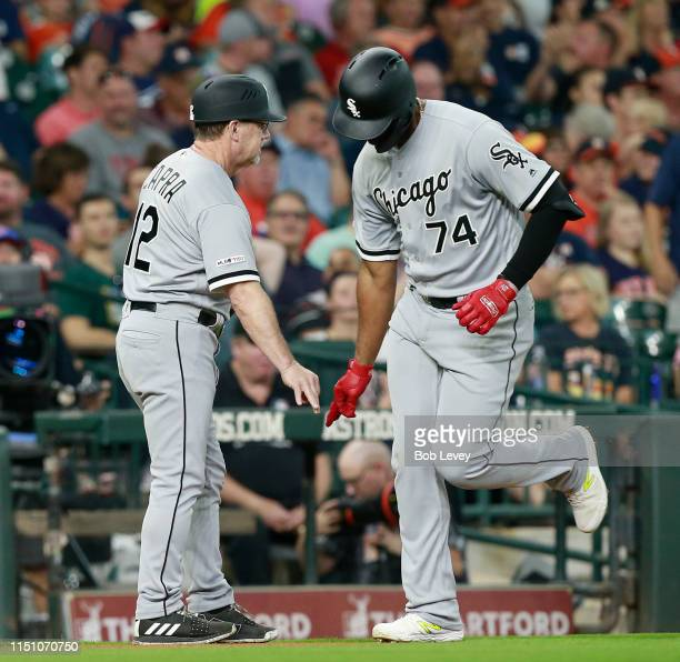 Eloy Jimenez of the Chicago White Sox receives congratulations from third base coach Nick Capra after hitting a home run in the first inning against...