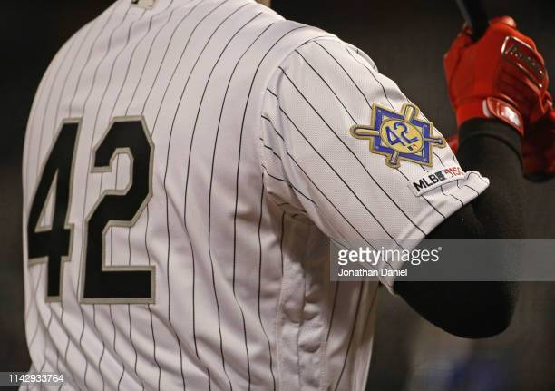 Eloy Jimenez of the Chicago White Sox shows a jersey and patch honoring Jackie Robinson during a game against the Kansas City Royals at Guaranteed...