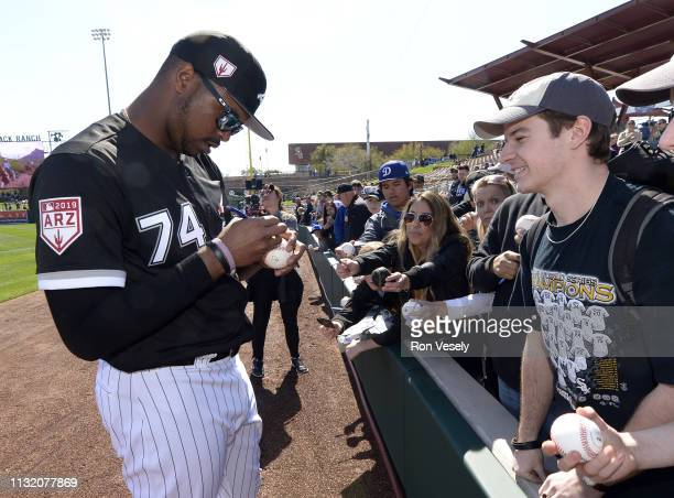 Eloy Jimenez of the Chicago White Sox signs an autograph prior to the game against the Los Angeles Dodgers on February 23 2019 at Camelback Ranch in...