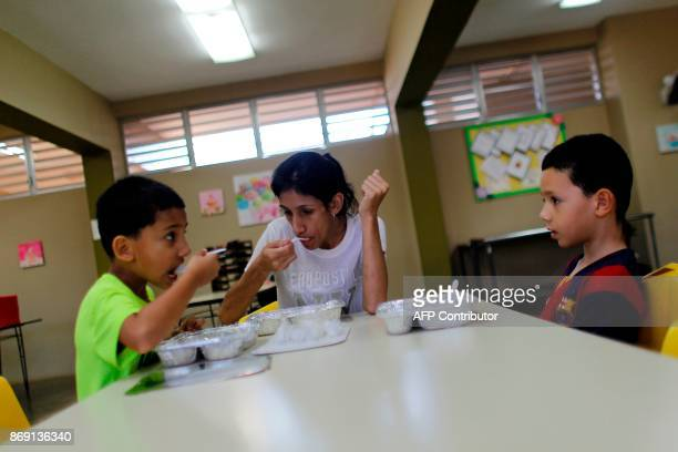 Elsa Diaz takes breakfast at the school canteen with her two children Angel Elier Rivera and Adriel Isaac Rosario in Barranquitas Puerto Rico October...
