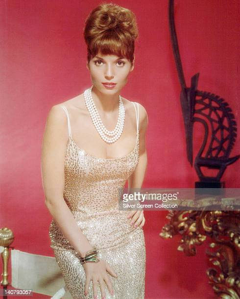 Elsa Martinelli Italian actress and fashion model wearing a pearl necklace and a thin strap sequinned dress in a studio portrait against a red...