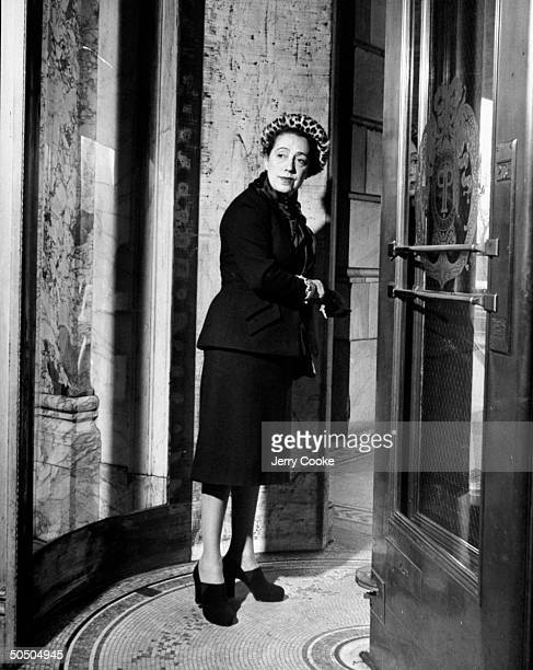 Elsa Schiaparelli standing in doorway at Plaza Hotel wearing suit and leopard hat