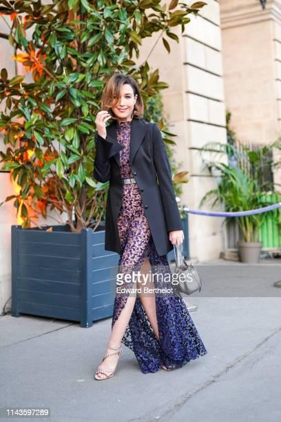 Elsa Zylberstein wears a long black jacket a transparent purple lace highcollar sideslit long dress a shiny silver belt a shiny silver bucket bag...