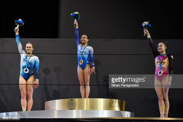 Elsabeth Black of Canada Morgan Hurd of The United States of America and Elena Eremina of Russia raise their arms as they pose with their medals from...