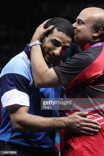 El-Sayed Lashin of Egypt celebrateswith the team coach after winning his Men's Singles Table Tennis second round match against Zoran Primorac of...
