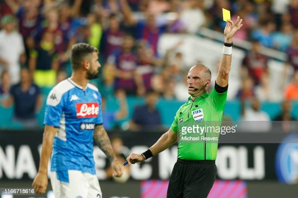 Elseid Hysaj of SSC Napoli receives a yellow card against FC Barcelona during the second half of a preseason friendly match at Hard Rock Stadium on...