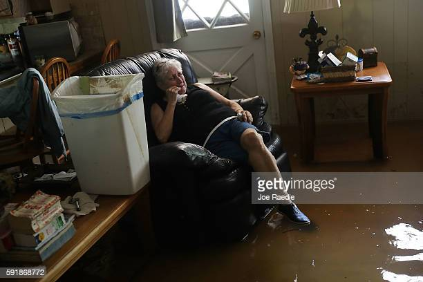 Elsie Lazarus is overcome with emotion as she sits in her flooded living room while retrieving what she can from her home on August 18, 2016 in St...