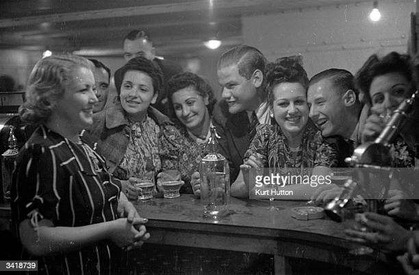 Elsie the barmaid chats to young couples in the Quarter Deck Bar at the Majestic Hotel in Onchan Head, Isle of Man, 9th September 1939. Original...