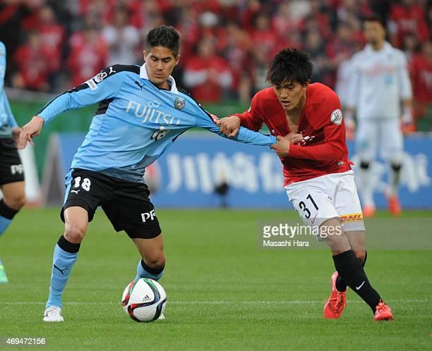 Elsinho of Kawasaki Frontale and Toshiyuki Takagi of Urawa Red Diamonds compete for the ball during the JLeague match between Kawasaki Frontale and...