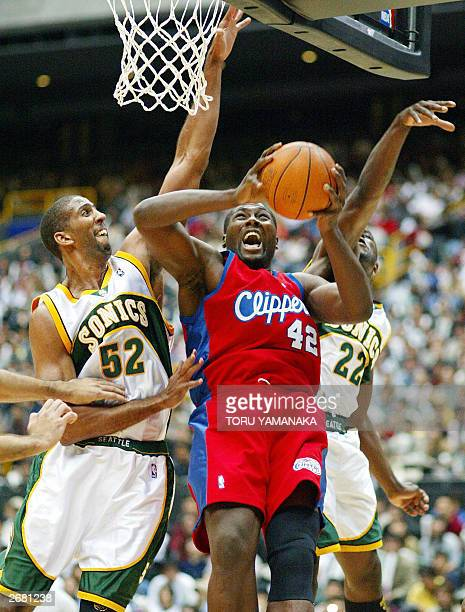 Elton Brand of the Los Angeles Clippers tries to shoot the ball as he battles with Calvin Booth and Ronald Murray of the Seattle SuperSonics during...