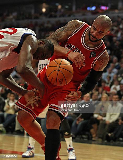 Elton Brand of the Philadelphia 76ers looses control of the ball next to Carlos Boozer of the Chicago Bulls at the United Center on March 28 2011 in...