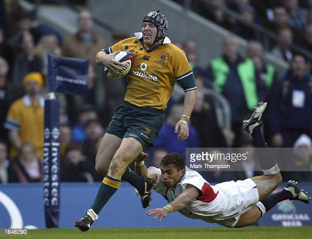 Elton Flatley of Australia evades the tackle from Jason Robinson of England to score the third try for Australia during the England v Australia...