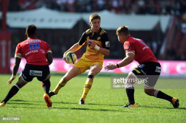 Elton Jantjies and Ruan Ackermann of Lions in action with Beauden Barrett of Hurricanes during the Super Rugby Semi Final match between Emirates...