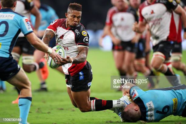 Elton Jantjies of the Lions passes as he is tackled during the round five Super Rugby match between the Waratahs and the Lions at Bankwest Stadium on...