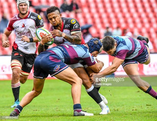 Elton Jantjies of the Lions tackled during the Super Rugby match between Emirates Lions and Reds at Emirates Airline Park on February 08, 2020 in...