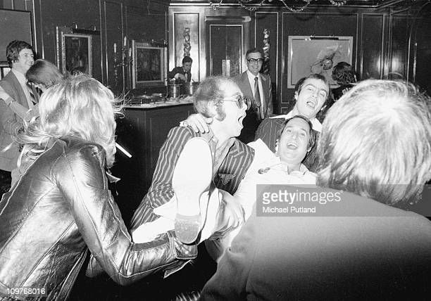 Elton John Neil Sedaka and Bernie Taupin partying in London England in 1975