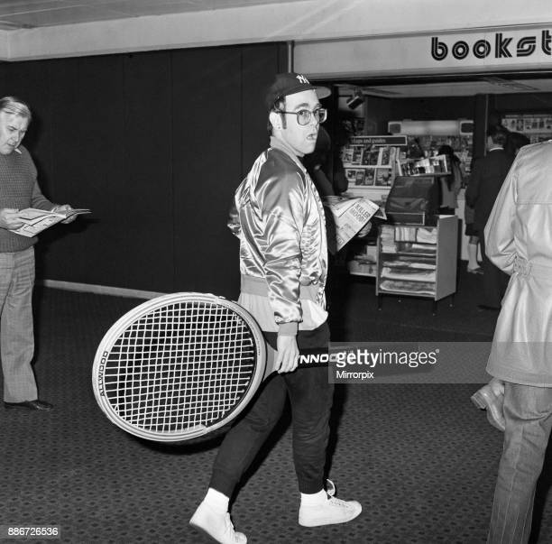 Elton John pictured at Heathrow Airport arriving back from America carrying a huge tennis racket 8th April 1978