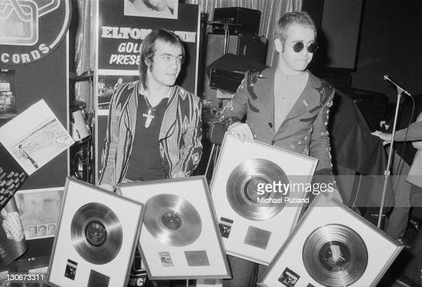 Elton John with his songwriting collaborator Bernie Taupin at a ceremony to award them gold discs for four of their cowritten albums 26th April 1973