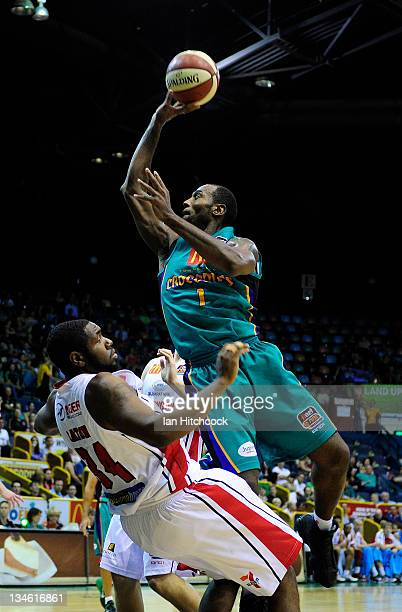 Elvin Mims of the Crococdiles makes a layup over Joevan Catron of the Hawks during the round nine NBL match between the Townsville Crocodiles and the...